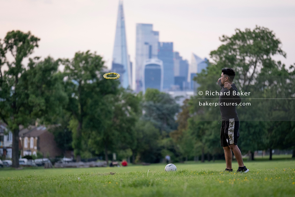 With the Shard and the capital's financial district in the distance, a young man throws a frisbee through the air towards an unseen opponent in Ruskin Park, on 7th June 2021, in south London, England.