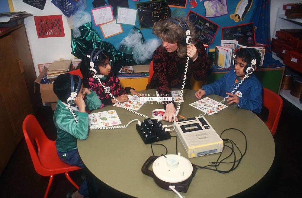 Junior school teacher and pupils using headphones and listening to tape machine,