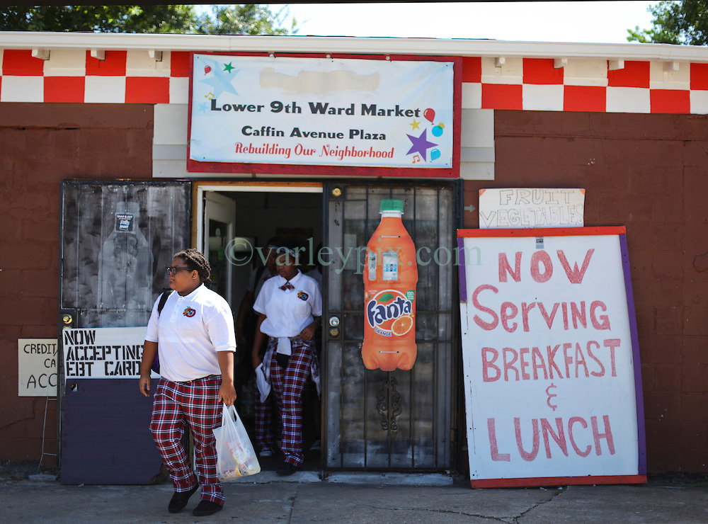 26 August 2015. New Orleans, Louisiana. <br /> Hurricane Katrina revisited. <br /> Rebuilding the Lower 9th Ward. <br /> Schoolgirls exit Galvez Goodies Grocery store, the only grocery store in the area classified as a 'food desert.' <br /> Photo credit©; Charlie Varley/varleypix.com.