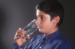Young boy drinking glass of water,