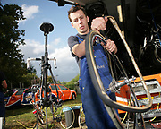 Ruud Beurskens, mechanic of the Rabobank cycling team, changing a tire after a stage during the 2008 Tour de France // Ruud Beurskens, mechanicien van de Rabobank-wielerploeg, verwisselt een band na afloop van een etappe van de Tour de France in 2008.