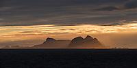Værøy islands rise over sea while illuminated by winter sunset, Moskenesøy, Lofoten Islands, Norway