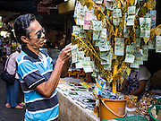30 DECEMBER 2015 - BANGKOK, THAILAND:  A man leaves an offering at a representation of a Bodhi tree in Bang Chak Market. Such trees are commonly used to raise money for religious purposes in Thailand. The market is supposed to close permanently on Dec 31, 2015. The Bang Chak Market serves the community around Sois 91-97 on Sukhumvit Road in the Bangkok suburbs. About half of the market has been torn down. Bangkok city authorities put up notices in late November that the market would be closed by January 1, 2016 and redevelopment would start shortly after that. Market vendors said condominiums are being built on the land.           PHOTO BY JACK KURTZ