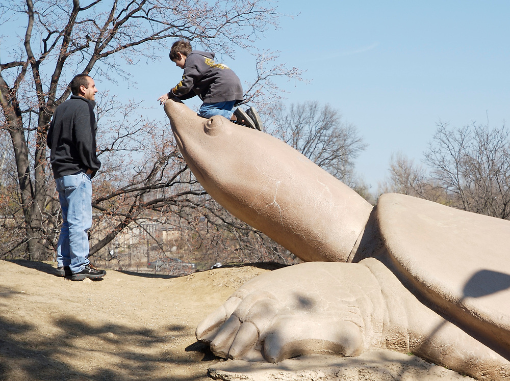 A child playing on a turtle sculpture in Turtle Playground on the edge of Forest Park in St. Louis, Missouri.  The turtles were designed and sculpted by Bob Cassilly.