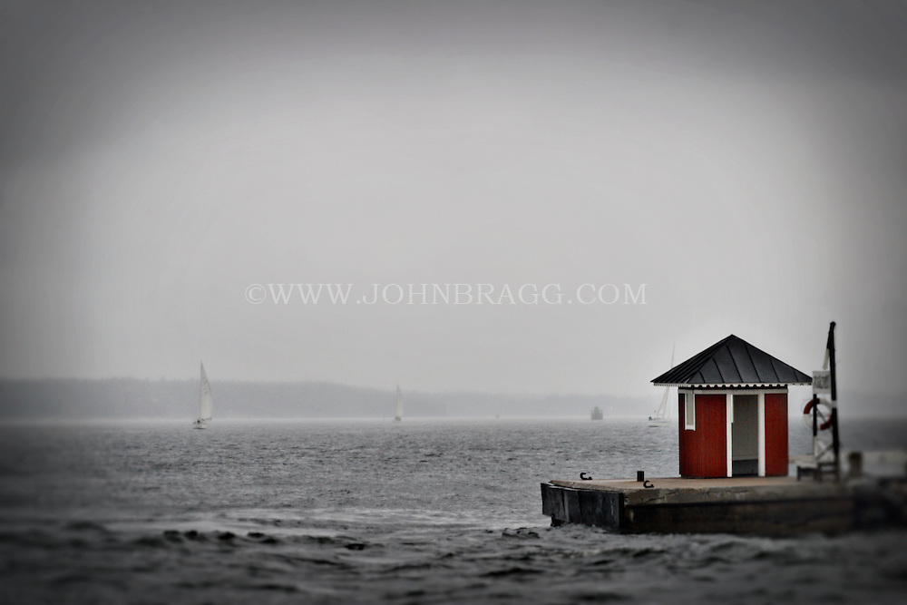 Sailboats on a gray, foggy day and a floating red hut on the Vaxholm Archipelago in Sweden