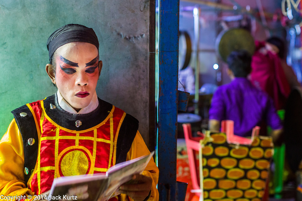 "25 JANUARY 2014 - BANG LUANG, NAKHON PATHOM, THAILAND: A performer backstage at a Chinese opera performance in a small town near Bang Luang, Nakhon Pathom, Thailand. Chinese opera was once very popular in Thailand, where it is called ""Ngiew."" It is usually performed in the Teochew language. Millions of Chinese emigrated to Thailand (then Siam) in the 18th and 19th centuries and brought their cultural practices with them. Recently the popularity of ngiew has faded as people turn to performances of opera on DVD or movies. There are still as many 30 Chinese opera troupes left in Bangkok and its environs. They are especially busy during Chinese New Year when travel from Chinese temple to Chinese temple performing on stages they put up in streets near the temple, sometimes sleeping on hammocks they sling under their stage.     PHOTO BY JACK KURTZ"