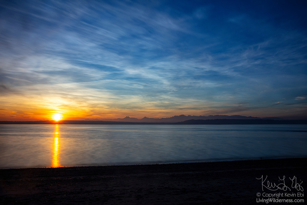 Sunglint stretches across the water of Puget Sound as the sun sets behind the Olympic Mountains in this view from Marina Beach Park, Edmonds, Washington.