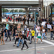 Protesters walk peacefully through downtown streets on Wednesday, June 3, 2020, in Orlando, Fla., over the death of George Floyd. Floyd died after being restrained by Minneapolis police officers on May 25.  (Alex Menendez via AP)