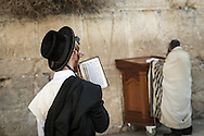 A young Haredy man with payot hairstile, with prayers book (siddur) in hand and tefillin in the forefront looks at an elder worshipper praying at the Kotel wrapped in a tallit shawl.