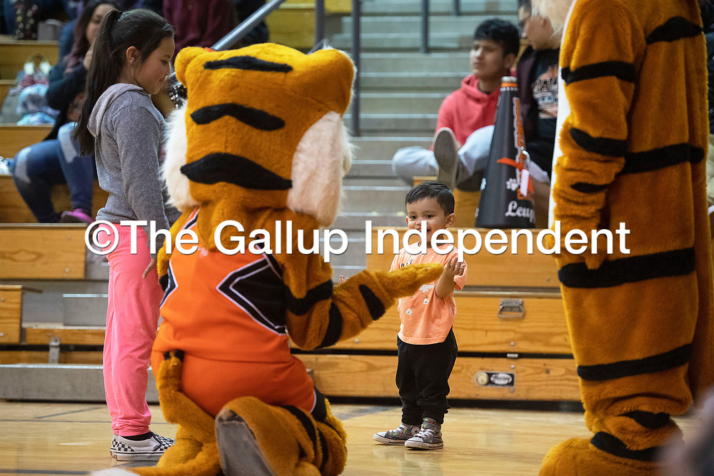 Big sister Ofelia Gonzales, left, watches her brother Christopher Trujillo interact with a Gallup Bengals mascot Friday night at the Gallup Shiprock game at Gallup High School.
