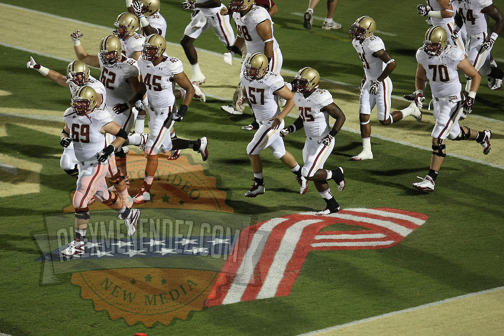 Boston College players enter the field over a ribbon in remembrance of 9/11, during an NCAA football game between the Boston College Eagles and the UCF Knights at Bright House Networks Stadium on Saturday, September 10, 2011 in Orlando, Florida. (AP Photo/Alex Menendez)