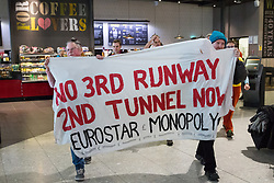 Campaigners against airport expansion from Rising Up stage a flashmob at Heathrow Airport's Terminal 2 on 18th February 2017 at Heathrow, United Kingdom. The activists were protesting against proposals to build a third runway at Heathrow Airport in order to permit an additional 250,000 flights a year.
