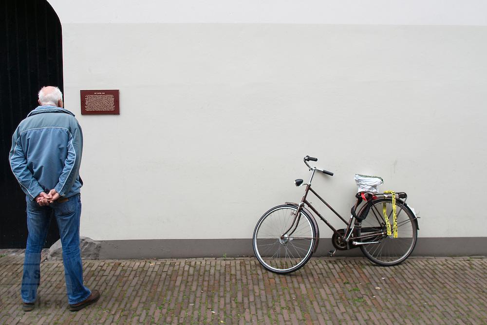 Een man leest aandachtig de tekst bij een oud pand in Utrecht.<br /> <br /> A man is reading the text on an old building in Utrecht.