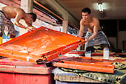"""26 SEPTEMBER 2012 - BANGKOK, THAILAND: Workers pack fresh fish in ice at a wholesale shop in Khlong Toey Market in Bangkok. Khlong Toey (also called Khlong Toei) Market is one of the largest """"wet markets"""" in Thailand. The market is located in the midst of one of Bangkok's largest slum areas and close to the city's original deep water port. Thousands of people live in the neighboring slum area. Thousands more shop in the sprawling market for fresh fruits and vegetables as well meat, fish and poultry.   PHOTO BY JACK KURTZ"""