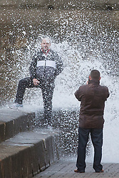 """© Licensed to London News Pictures. 09/11/2015. Bridlington, UK. A man poses for a photograph on the sea defences at the sea side town of Bridlington & gets caught out by a huge wave. The Yorkshire region was hit by severe gales this afternoon with winds up to 60mph. The Met Office warned West Yorkshire to expect gales and locally severe gales over high ground, with some """"very gusty"""" winds to the east of high ground as well.<br /> Photo credit: Andrew McCaren/LNP"""