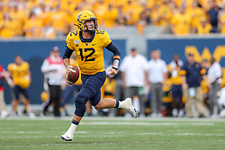 Sep 14, 2019; Morgantown, WV, USA; West Virginia Mountaineers quarterback Austin Kendall (12) rolls out to pass during the first quarter against the North Carolina State Wolfpack at Mountaineer Field at Milan Puskar Stadium. Mandatory Credit: Ben Queen-USA TODAY Sports