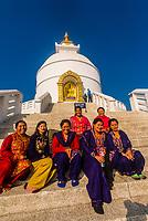 Nepali women sit for a portrait in front of the Shanti Stupa (The World Peace Pagoda) on Anadu Hill, above Pokhara, Nepal.
