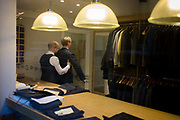 A gentleman client has a fitting for a new made-to-measure suit, seen through a City taylor's window. Feeling under the arm of his client, the taylor makes sure his measurements are correct before making final adjustments for the final garment. Hanging in the shop are other suits and jackets, awaiting buyers in the backstreet in the City of London, the capital's financial heart, founded by the Romans in 43AD.