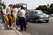 Teenage girls in school uniforms purchase cold treats made of crushed ice and sweet syrup called granizado from a street merchant in central Havana, Cuba on Friday June 27, 2008.