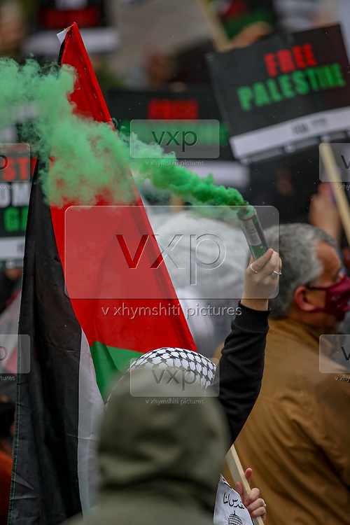 """Leicester, United Kingdom, May 21, 2021: People holding placards, banners and waving Palestinian flags gathered to support the """"Palestine Action"""" activists group who occupied the building of the Israeli-owned Elbit-Thale Systems subsidiary UAV Tactical Systems in the city of Leicester United Kingdom on Friday, May 21, 2021. Three days ago activists sprayed red paint on the building and demand that it shuts down. The company's operations are at a halt for three consecutive days now with police negotiating a truce between activists and the company. Activists argue that the drones being manufactured in the facility are being used in indiscriminate attacks against the Gaza Strip. (Photo by Vudi Xhymshiti)"""