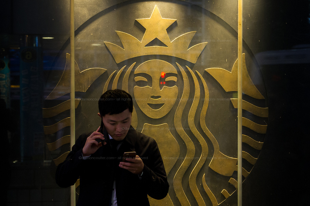 A Japanese salaryman or office worker uses a smart phone and an ordinary cellphone as he waits outside the Starbucks cafe in Shibuya, Tokyo, Japan, Friday December 14th 2018