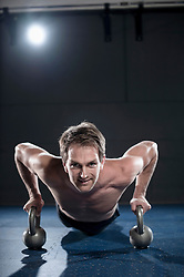 Athlete doing workout in fitness studio with Kettlebell, Bavaria, Germany