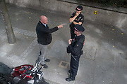 The rider of a motorbike who has been stopped by City of London Police, talks to officers at the roadside in the Square Mile, the capitals financial district, on 6th August 2020, in London, England.