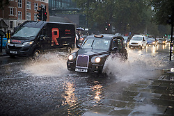 © Licensed to London News Pictures. 14/09/2021. London, UK. Traffic ploughs through surface water on the Euston road in North London during heavy rainfall. Heavy rain is expected to cause flash flooding in parts of the UK. Photo credit: Ben Cawthra/LNP