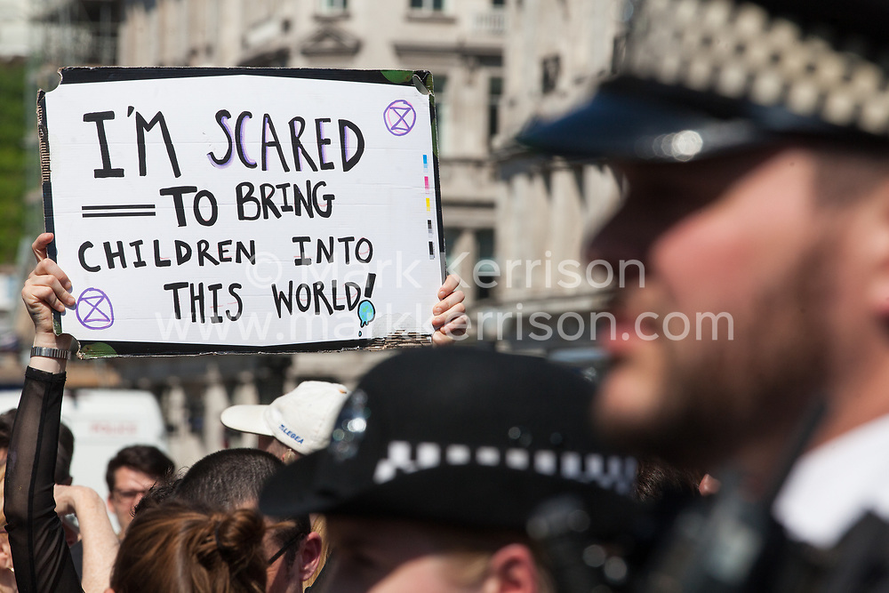 London, UK. 20th April 2019. Police officers move in to arrest climate change campaigners from Extinction Rebellion who had locked themselves using arm tubes at Oxford Circus following a policing operation to clear it of protesters earlier in the day. The heart of London's shopping district was blocked again for around two hours by the lock-ons on the sixth day of International Rebellion activities to call on the British government to take urgent action to combat climate change.
