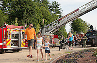 Adeline, Cora and Alex Takantjas enter Sargent Park for Belmont Police Department's National Night Out on Tuesday evening.  (Karen Bobotas/for the Laconia Daily Sun)