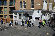 As the UK's Coronavirus death toll during the government's social distancing lockdown, rose by 384 to 33,998, and the R rate of infection is reported to be between 0.7 and 1.0, south Londoners queue around the corner of  Pensose Street and Walworth Road to access the branch of Barclays Bank, on 15th May 2020, in London, England.