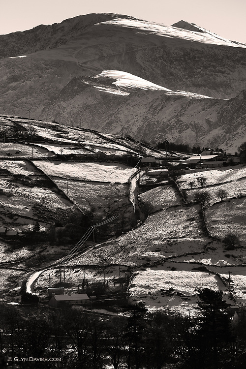 The narrow lane winding up through the slate quarrying village of Deiniolen, disappears over the ridge but in the distance the Snowdon railway track leads us up to the summit of the highest mountain in England and Wales
