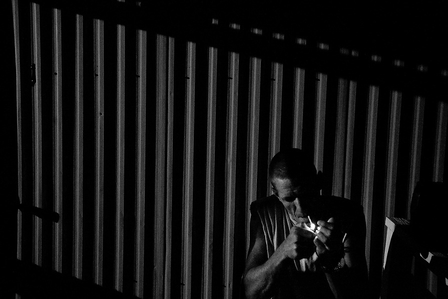 Recovering cocaine addict, Benji A. lights up a cigarette before going to sleep on his fifth night at Recovery Works.