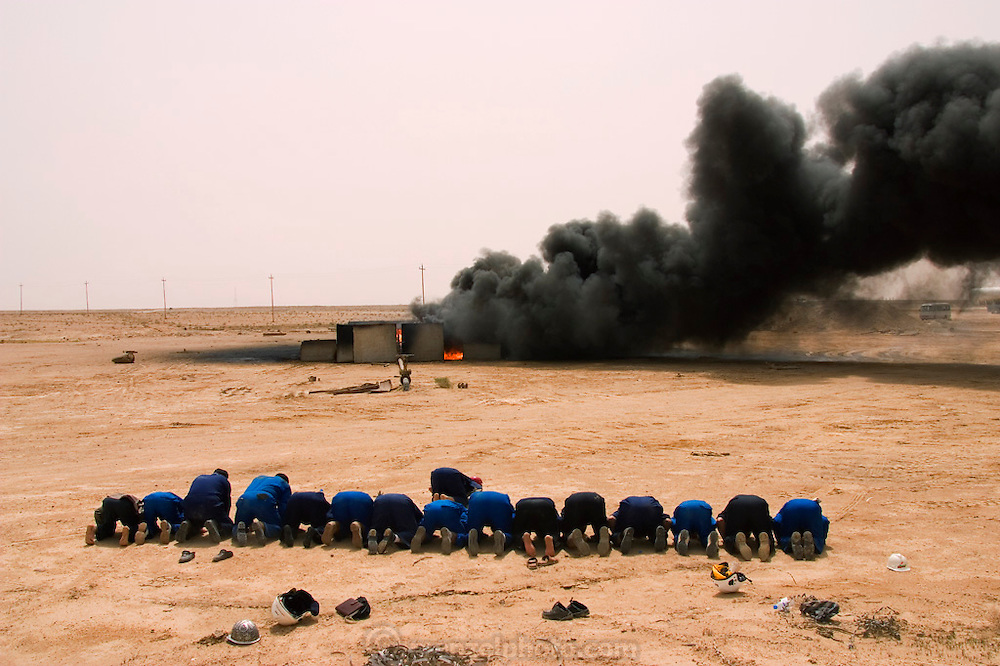 "Burning oil well in the Rumaila Oil Field in southern Iraq. The wells were ignited by retreating Iraqi troops when the US and UK invasion began in March 2003. Firefighters from the Kuwait Oil Company (called KWWK: Kuwait Wild Well Killers) pray at noon by the first oil well fire they were working on in Iraq's Rumaila Oil field. Later in the day they extinguished this smoky fire and the next day stopped the flow of gas and oil with drilling mud using what is called a ""stinger,"" a tapered pipe on the end of a long steel boom controlled by a bulldozer. Drilling mud, under high pressure, is pumped through the stinger into the well, stopping the flow of oil and gas. The Rumaila field is one of Iraq's biggest oil fields with five billion barrels in reserve. Rumaila is also spelled Rumeilah."