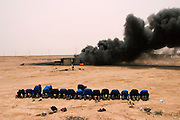 """Burning oil well in the Rumaila Oil Field in southern Iraq. The wells were ignited by retreating Iraqi troops when the US and UK invasion began in March 2003. Firefighters from the Kuwait Oil Company (called KWWK: Kuwait Wild Well Killers) pray at noon by the first oil well fire they were working on in Iraq's Rumaila Oil field. Later in the day they extinguished this smoky fire and the next day stopped the flow of gas and oil with drilling mud using what is called a """"stinger,"""" a tapered pipe on the end of a long steel boom controlled by a bulldozer. Drilling mud, under high pressure, is pumped through the stinger into the well, stopping the flow of oil and gas. The Rumaila field is one of Iraq's biggest oil fields with five billion barrels in reserve. Rumaila is also spelled Rumeilah."""