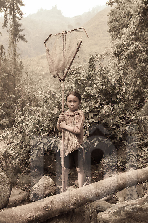 A young Hmong girl holding a fishing net pauses and looks at the camera during her walk up the stream for morning fishing, <br /> Than Uyen area, Lai Chau, Vietnam, Southeast Asia