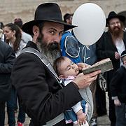 Jérusalem, israël, le jeudi 21 avril 2011 - près de 10 000 fidèles étaient rassemblés au mur des lamentations pour la bénédiction des Cohanim (prêtres juifs) au quatrième jour de Pessah (Pâques juive). Un homme récite ses prières avec son enfant.