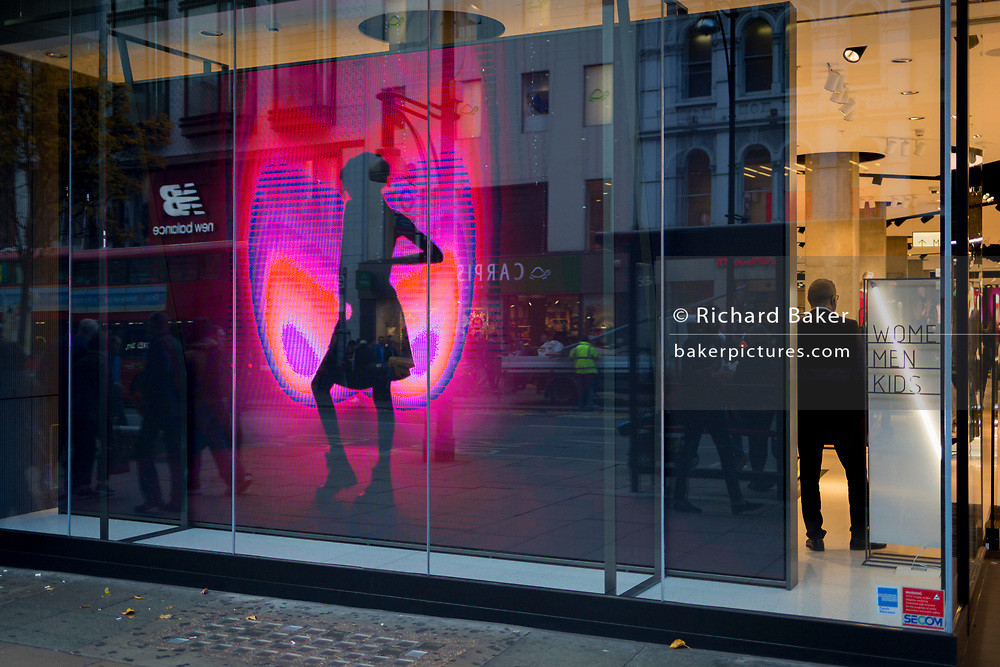 A security guard stands next to the Christmas video ad loop in the London retailer 'Reserved', on Oxford Street, on 22nd November 2017, in London England.