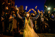 Jasmine Fallstich, middle, of Oakland, raises her hands up in with other protesters in demonstration in front of the police in Oakland, Friday, May 29, 2020. Demonstrators gathered Friday night in Oakland to protest the death of Minneapolis man George Floyd.