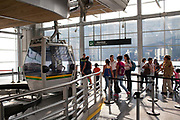 People queueing for the cable car that rides above the city of Medellin, Colombia. The cable car has two sections - one which is used as transport for one of the poorest neighbourhoods in the city. The second section links to Arvi park and is aimed more at tourists and visitors, connecting the city with the large urban park.