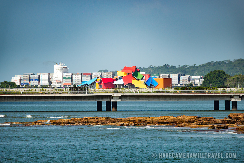 A large container ship heading into the entrance of the Panama Canal moves behind the colorful rooftop of the Biomuseo designed by Frank Gehry. In the foreground is part of the new Coastal Beltway (Cinta Costera), a controversial ring road several hundred feet out along the waterfront of the historic district of Casco Viejo.