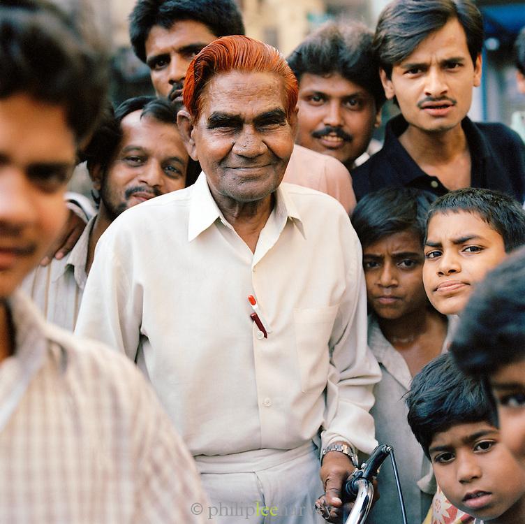 Portrait of an elderly man with henna dyed red hair in crowd, Lucknow, Uttar Pradesh, India