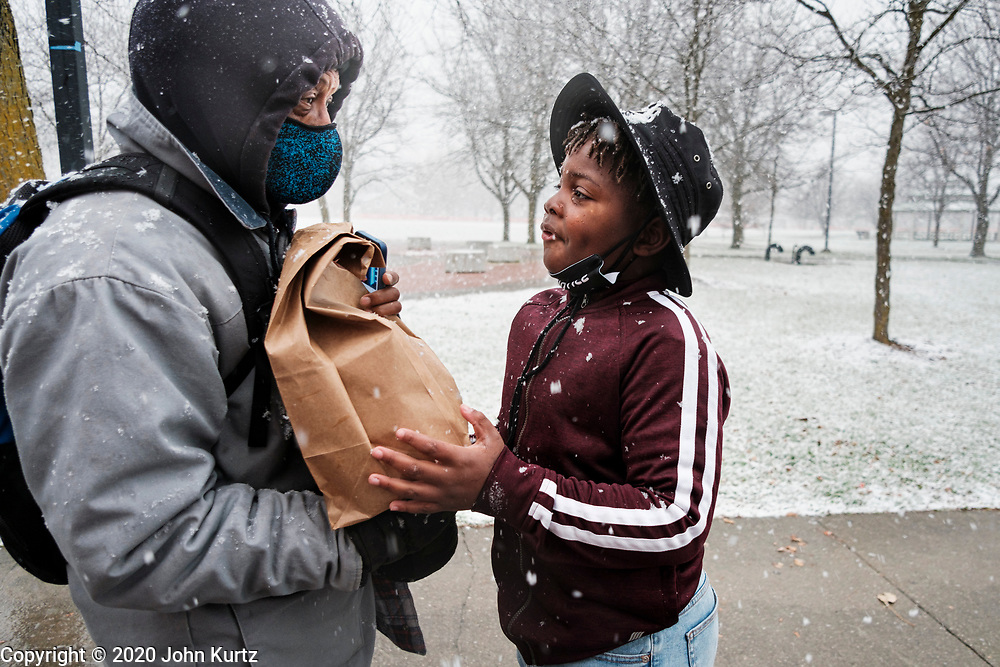 23 NOVEMBER 2020 - DES MOINES, IOWA: A child volunteering at a food distribution (right) hands a bag of food to a person in line during a Thanksgiving food distribution at a park in Des Moines during a snowstorm. The food distribution was organized by Urban Dreams, a community empowerment NGO in central Des Moines, and the NAACP. The food was provided by Hy-Vee, a regional grocery store chain based in Des Moines. They had about 450 meals available. A spokesperson for Hy-Vee said the company was giving away more than 20,000 Thanksgiving meals this year. The Food Bank of Iowa said food insecurity in Des Moines has doubled since the start of the Coronavirus pandemic.   PHOTO BY JACK KURTZ