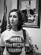 17 OCTOBER 2013 - PHOENIX, AZ:  MOLLY DURAN, a civil rights protester, stands in front of the official portrait of Arizona Attorney General Tom Horne during a protest in his office. About 100 people came to the office of Arizona Attorney General Tom Horne to protest the decision by Horne to sue community colleges in Maricopa County that charge DREAM Act students who are residents of Arizona out of state tuition rather than in state resident tuition. Nearly 10 people were arrested in a planned civil disobedience during the protest.     PHOTO BY JACK KURTZ