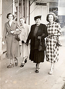 happy smiling female only family group together walking in the street France ca 1950s