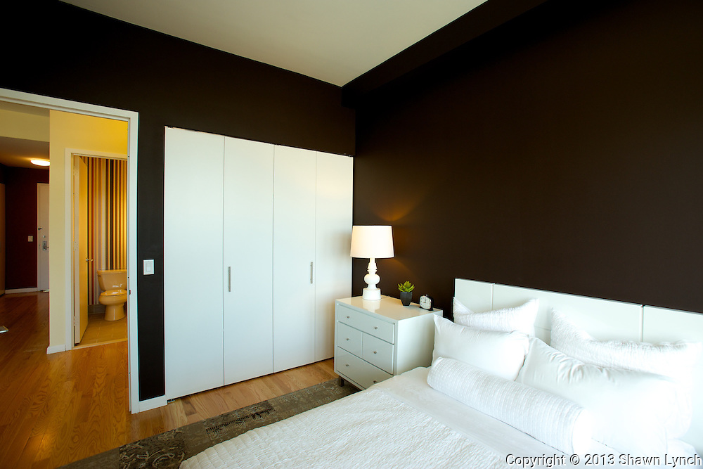 A dark brown bedroom located inside a model apartment at the Queens West Building 2 in Long Island City, New York provides a nice sense of warmth and comfort.