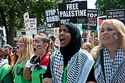 Protest against Israel's latest attack on Gaza, July 19th 2014. A line of young women with Palestinian stickers on their faces lead the march.