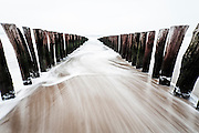 A Line of wooden posts at the coast with a wave going out. Zeeland, The Netherlands.