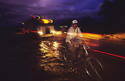 Central America, Honduras, Choluteca. Devastation in the aftermath of Hurricane Mitch. High winds and flooding. Soil erosion caused by deforestation. Man with bicycle and truck navigate on rainswept roads. Infrastructure destroyed.