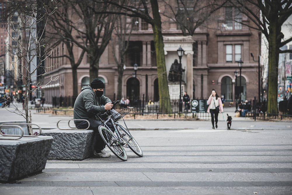New York City, USA - March 19, 2020: A man wearing a face mask sits with his bicycle in Cooper Square in the East Village area of Manhattan. Days earlier the city declared a state of emergency due to the growing coronavirus pandemic.
